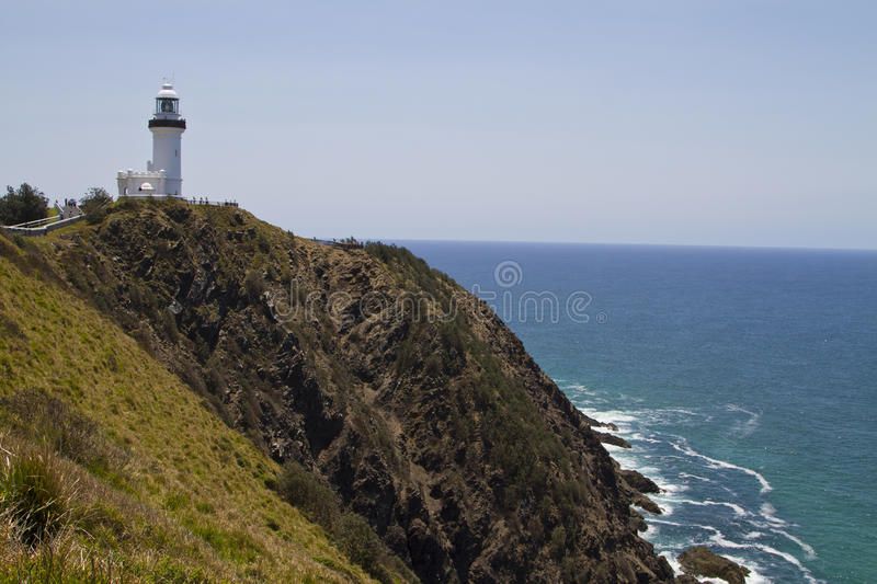 Ocean view with the Cape Byron lighthouse. (Byron Bay, New South Wales, Australia). The lighthouse is on the top of the bald rocky headland royalty free stock image