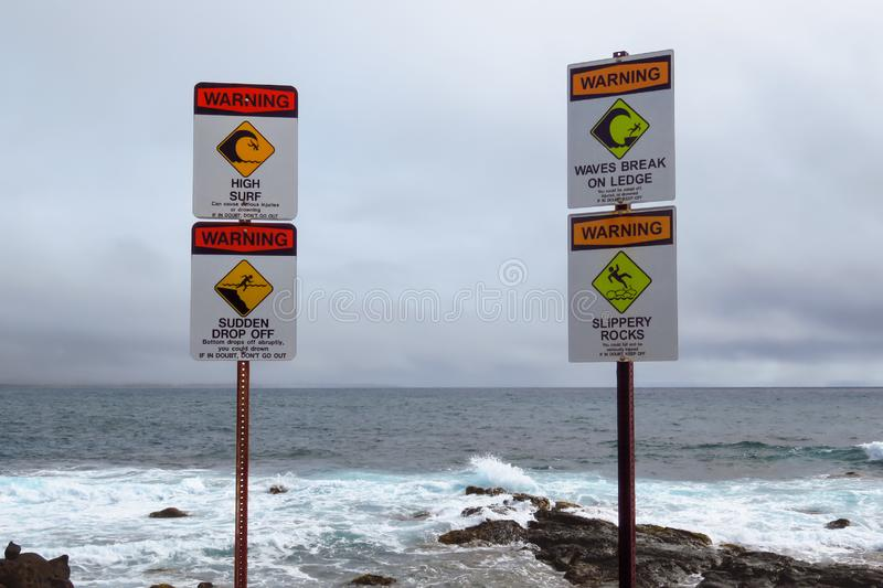 Ocean warning pictographs `High Surf` `Sudden Drop Off` `Waves Break On Ledge` `Slippery Rocks`, Kauai, Hawaii, USA. Sea warning signs `High Surf` `Sudden Drop royalty free stock photography