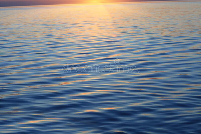 Ocean water background, golden sunset or sunrise at sea. Scenic ocean water background, golden sunset or sunrise at sea royalty free stock images