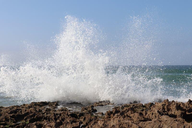 Ocean water beat against beach rocks royalty free stock photos