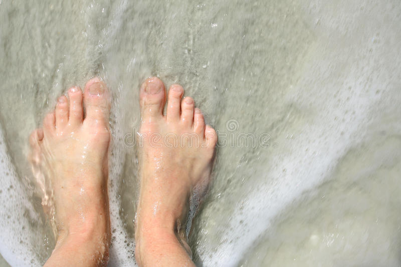 Ocean Water Rushing Over Woman's Feet. Close up portrait of a woman's feet standing on the beach shore as the ocean waves wash over them royalty free stock images