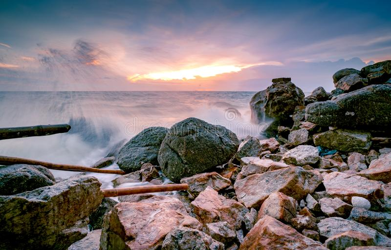 Ocean water splash on rock beach with beautiful sunset sky and clouds. Sea wave splashing on stone at sea shore on summer. Nature royalty free stock images