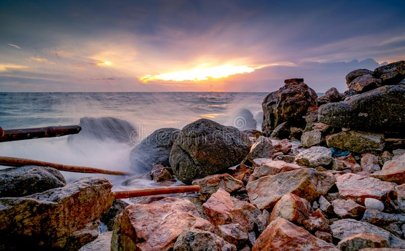 Ocean water splash on rock beach with beautiful sunset sky and clouds. Sea wave splashing on stone at sea shore on summer. Nature royalty free stock photo