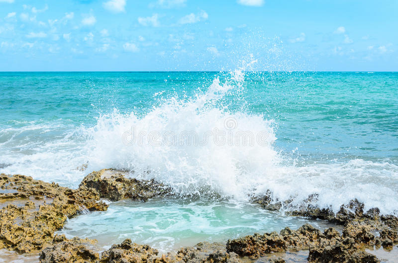 Ocean water splashing on rocks and forming a natural pool in the center of the image. Sunny day, very beautiful, with water hitting rocks and throwing many royalty free stock image