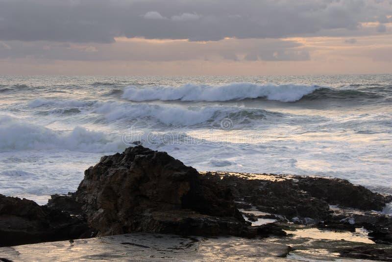 Ocean wave against rocks royalty free stock photos