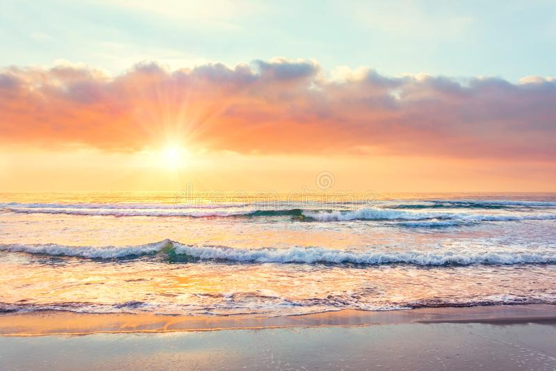 Ocean wave on the beach at sunset time, sun rays stock photo