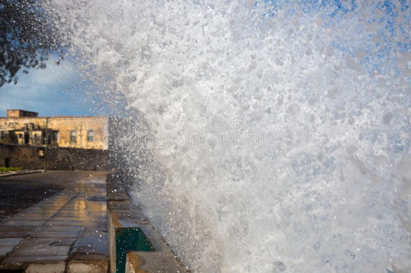 An ocean wave crashes over a seawall to a photographer and to seafront embankment close up. Mozambique island. Indian ocean coast. royalty free stock photo