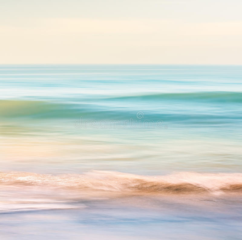 Ocean Wave Motion. A high-key seascape featuring ocean waves with blurred panning motion. Image displays subtle cross-processing and light, pastel colors stock images