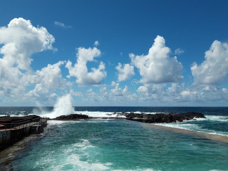 Ocean wave splash on rocks at coast on a sunny day with blue sky stock photos