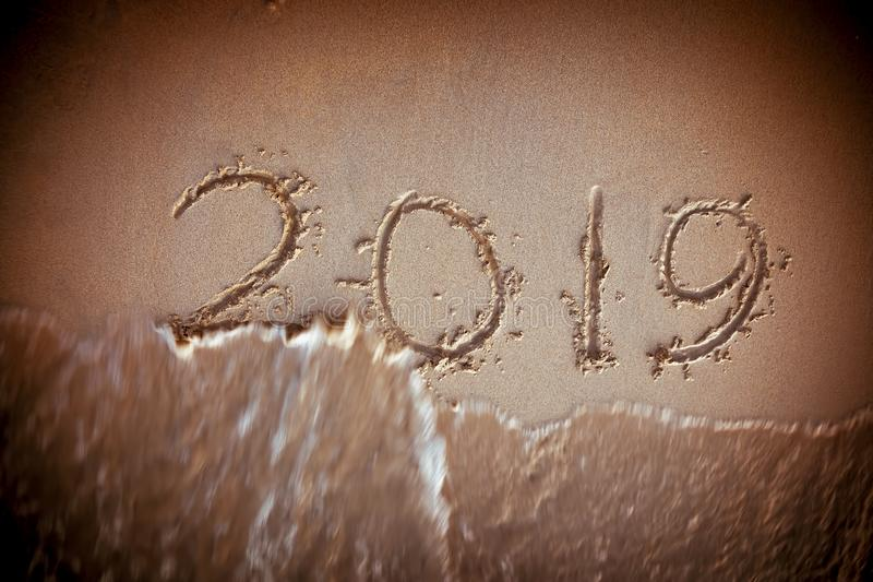Ocean wave Washing Away 2019 Year. Handwritten On Sandy Beach stock image
