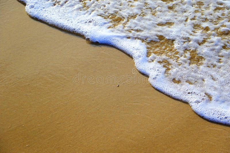 Ocean wave washing up sandy beach with bubbles and foam stock photography