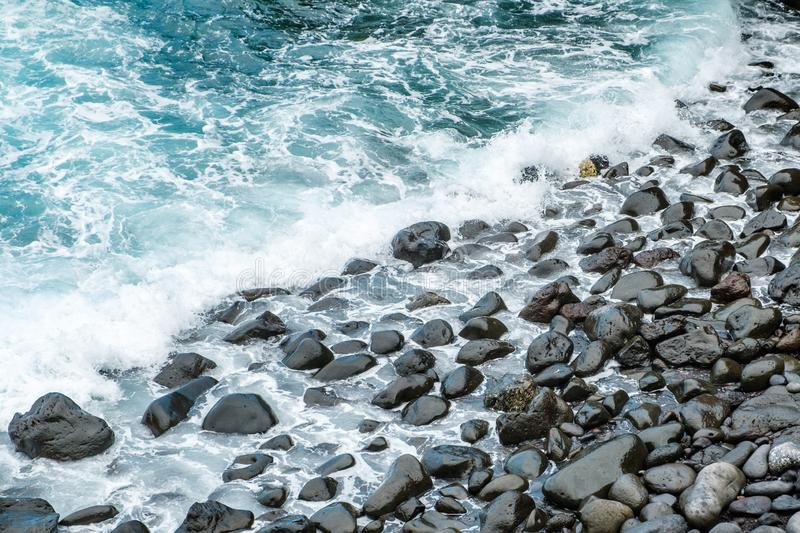 Ocean waves on black pebble stone coast.  stock images