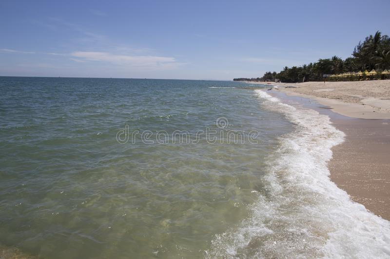 Ocean waves clap onto sunny sandy beaches and blue clouds stock image