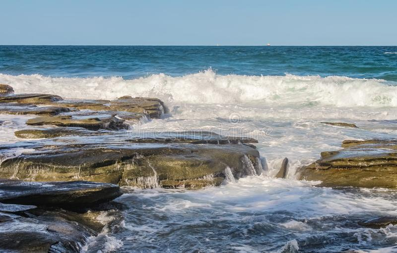 Ocean waves crash against eons old volcanic rock and water runs and breaks the stone - with tiny boats on the horizon royalty free stock photos