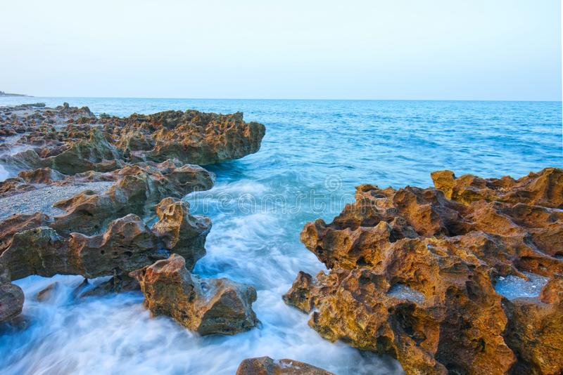 Ocean And Limestone Rock Formations. Ocean waves crashing against limestone rock formations royalty free stock photography