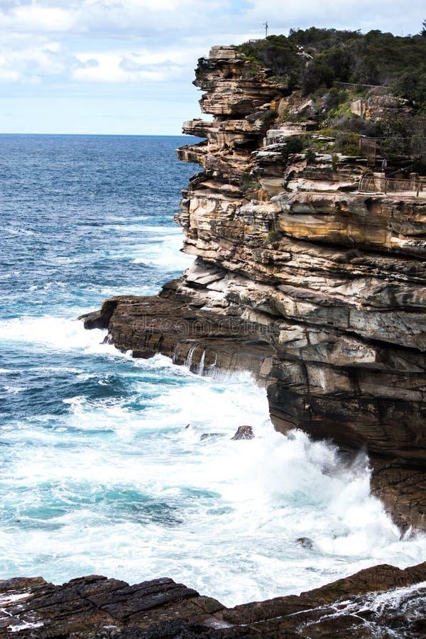 Ocean waves crashing onto jagged rock cliff face royalty free stock image