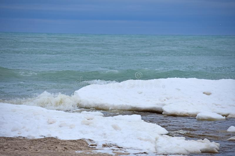 Ocean waves with ice boulders on shore stock images