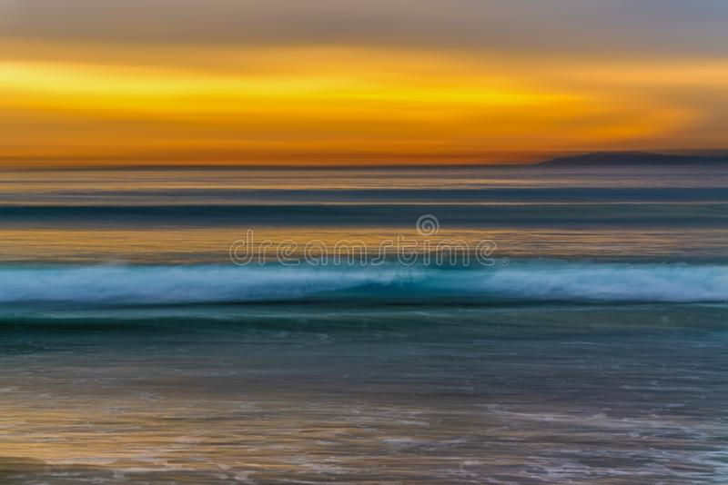 Sunset on the beach, ocean waves and yellow sky royalty free stock images