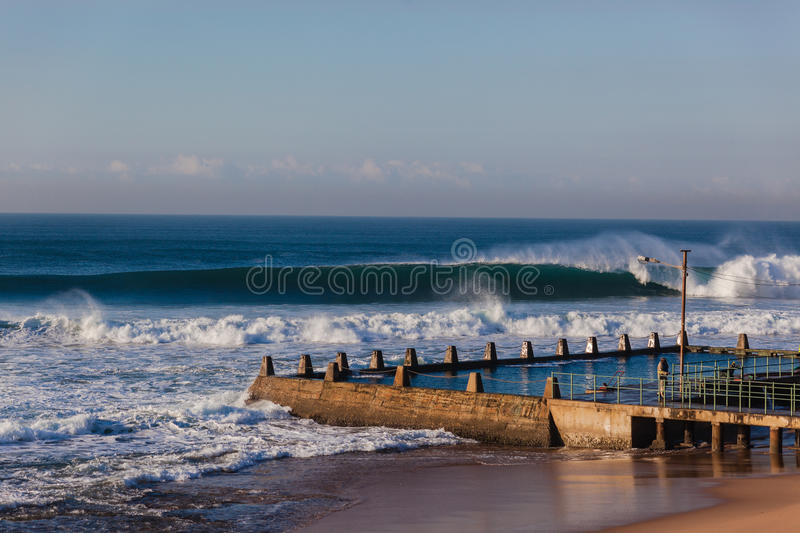Ocean Waves Tidal Pool. Winter morning ocean waves of good shape crashing surging onto shallow reefs in front of concrete tidal pool royalty free stock photography