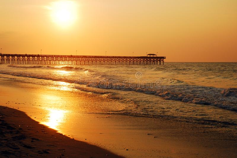 Oceanfront Sunrise and High tide. The sun rises near the pier in Myrtle Beach, South Carolina stock photos