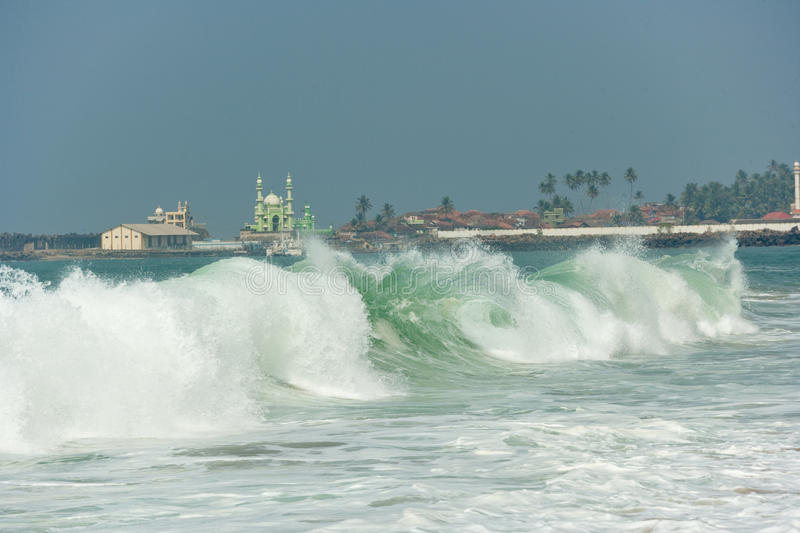 Oceanic wave and minaretes at background. The wave features brilliant green colors and white foam. The wave is curling over ending in crashing white foam that royalty free stock photography