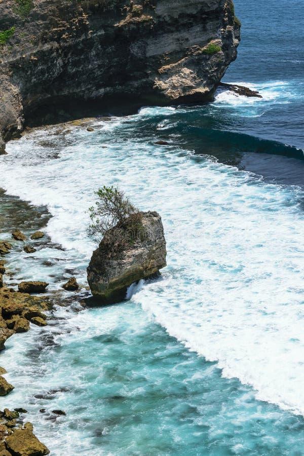 Oceano Índico azul que lava o penhasco e a praia com as rochas enormes em Bali, Indonésia fotos de stock royalty free