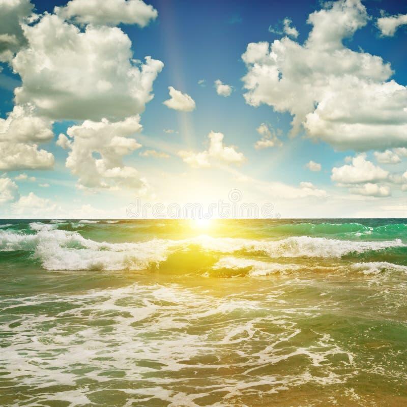 Oceano, Sandy Beach, céu azul e nascer do sol imagem de stock