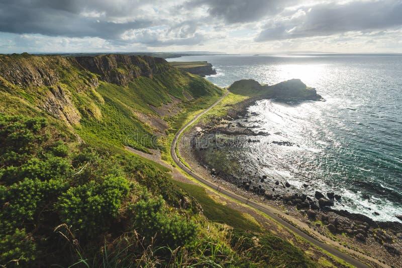 Oceano soleggiato, riva verde con la strada l'irlanda immagine stock libera da diritti