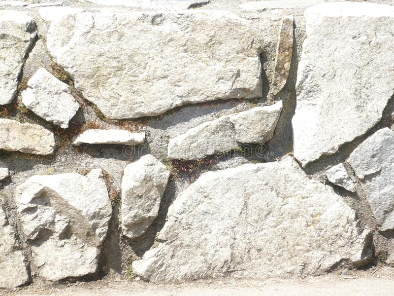 Oceanside Stone Wall. The white and grey colouring of the rock is offset by deeper grey spaces.  Suitable for a background stock photo