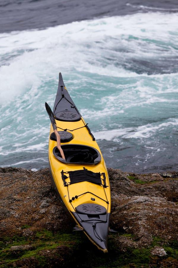 Oceanu kajak wyrzucać na brzeg na skalistym brzeg przy pływowymi gwałtownymi fotografia royalty free