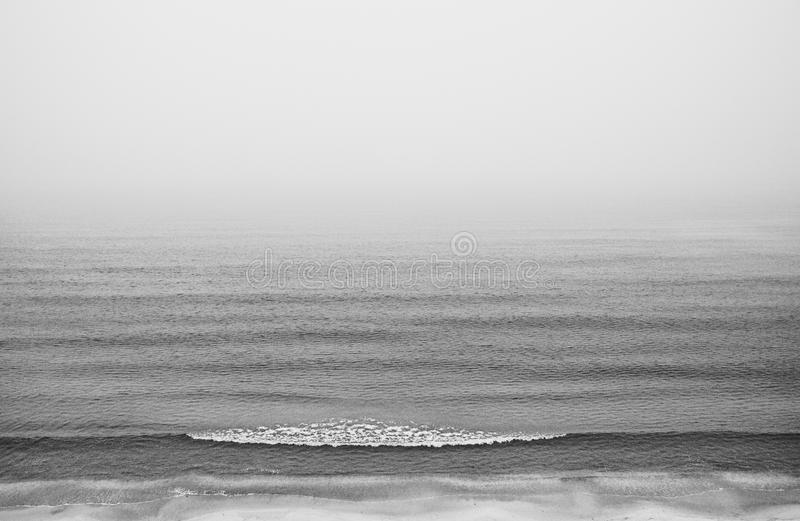 Beach in the fog, in a minimalist style, with no horizon. Background. Black and white. Seacoast in the fog, in a minimalist style, with no horizon. Background royalty free stock images