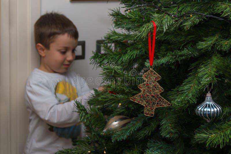 Ocho años del muchacho de bolas y decoraciones de la ejecución en el árbol de navidad fotos de archivo