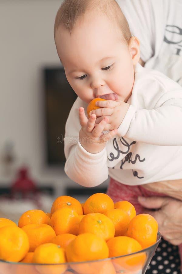 Ocho meses del bebé que chupa una mandarina fotografía de archivo