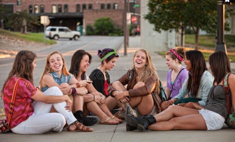 Ocho muchachas bonitas que se sientan al aire libre imagenes de archivo