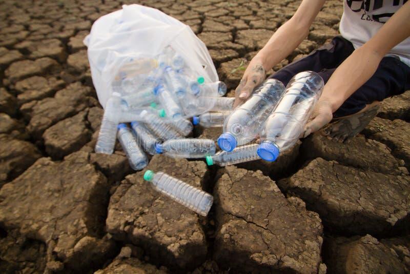 Ochotnicza chłopiec podnosi w górę klingerytu odpady i butelka klingerytu zdjęcie royalty free