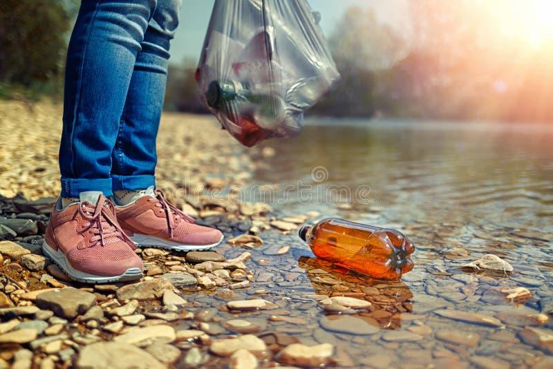 Ochotnicza pozycja na banku rzeka i unosi? si? w rzecznej plastikowej butelce, Poj?cie ochrona obraz royalty free