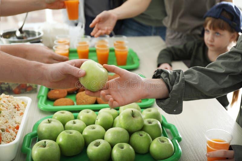 Ochotniczy daje jabłko biedna kobieta indoors zdjęcia stock