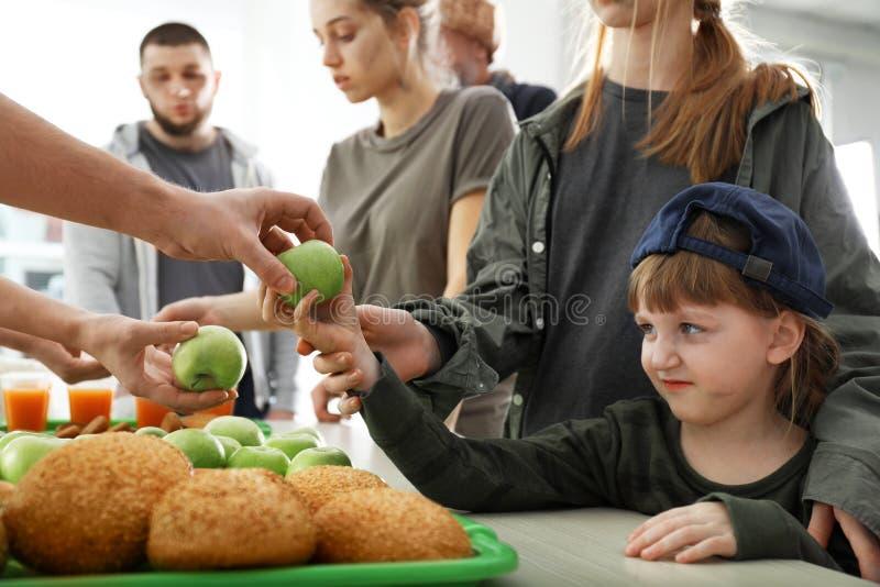Ochotniczy daje jab?ko biedna dziewczyna obrazy royalty free