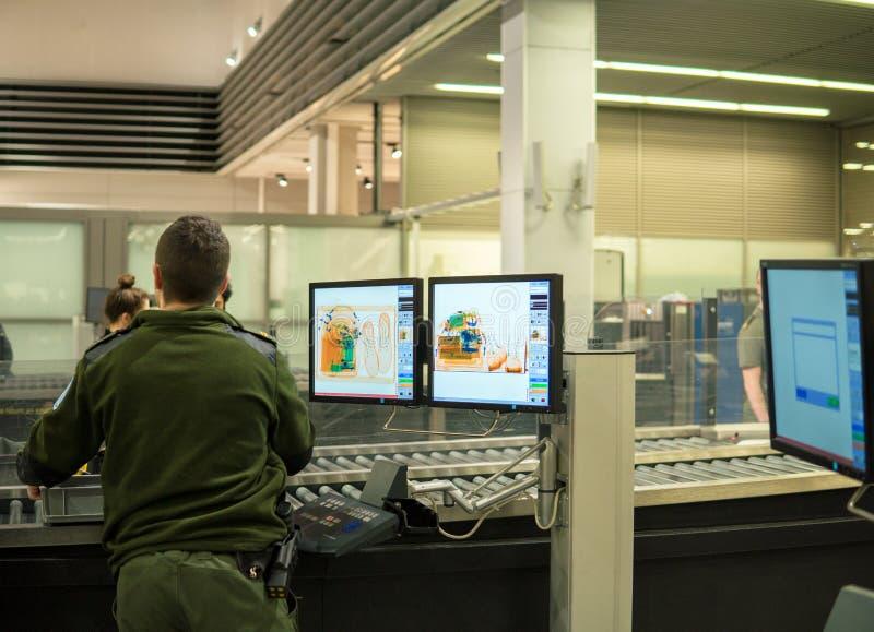Ochrona lotniska czeka punkt z monitorami i X promienia scaner pożyczający Obyczajowy ochrona pracownik sprawdza bagaż goście fotografia royalty free