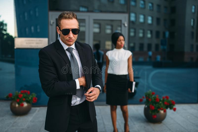Ochroniarz w kostiumu i okularach przeciwsłonecznych, kobieta VIP fotografia stock