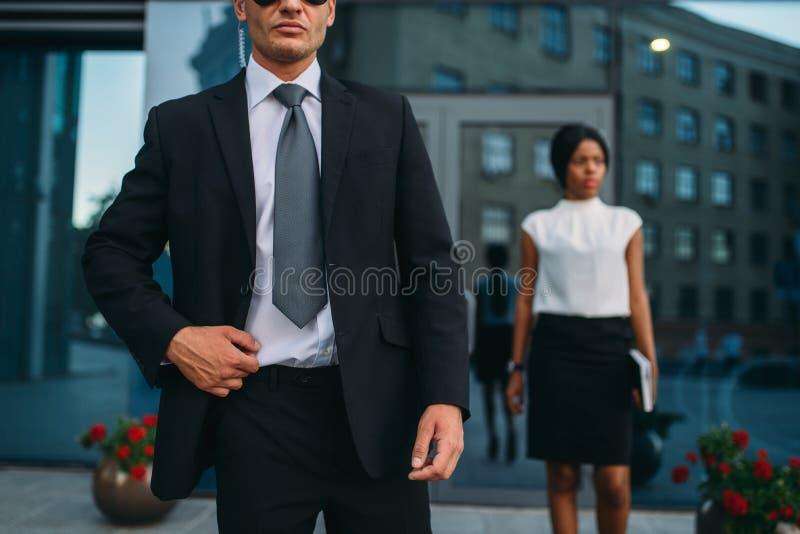 Ochroniarz w kostiumu i okularach przeciwsłonecznych, kobieta VIP zdjęcie royalty free