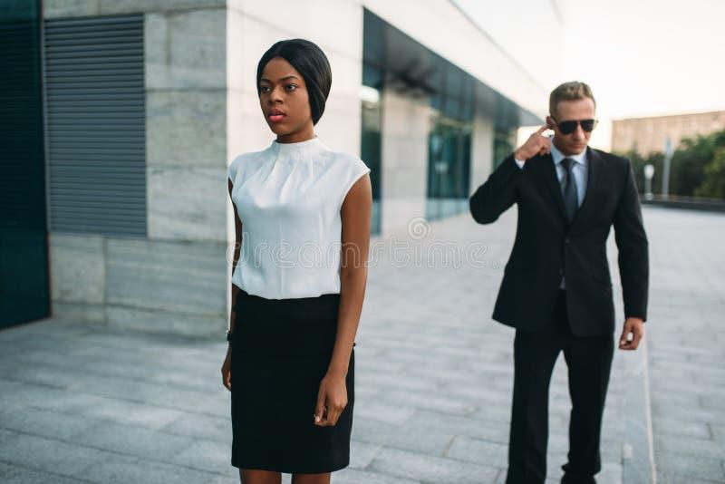 Ochroniarz w okularach przeciwsłonecznych i czarnej biznesowej kobiecie fotografia stock