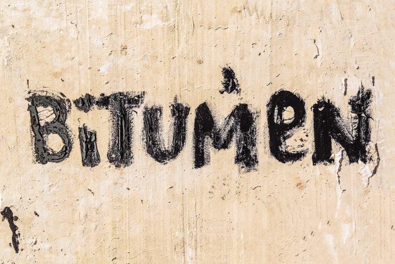 Ochronny bitumu mastyks na betonowym bruku Bitum - czarny bitumiczny słowo zdjęcie royalty free