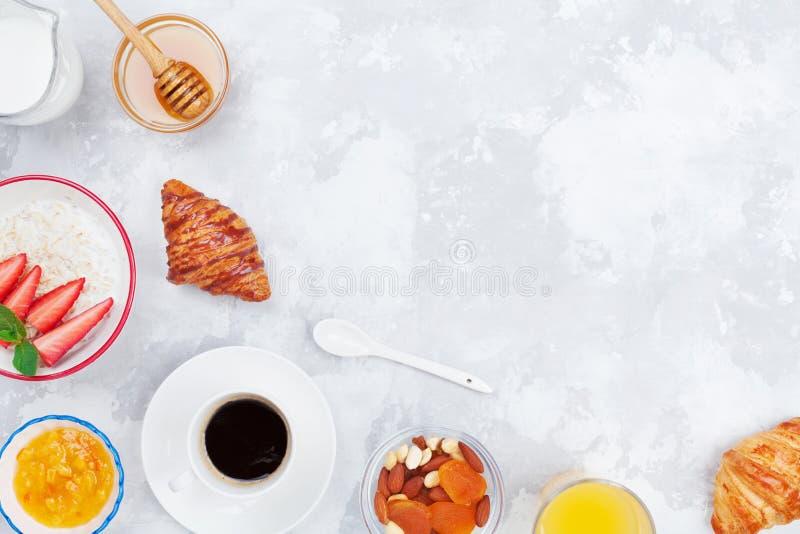 Ochtend continentaal ontbijt met koffie, croissant, havermeel, jam, honing en sap op de bovenkantmening van de steenlijst vlak le stock fotografie