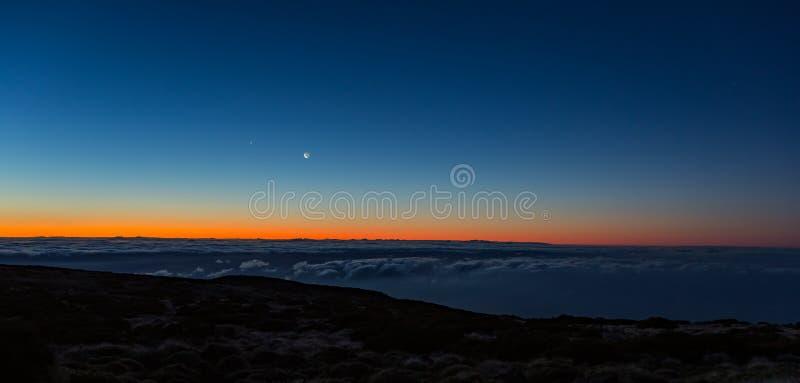 Ochtend donkere zonsopgang met blauwe hemel en gouden geeloranje kleur boven horizon Nachtlichten van Gran Canaria-Eiland tussen royalty-vrije stock afbeelding