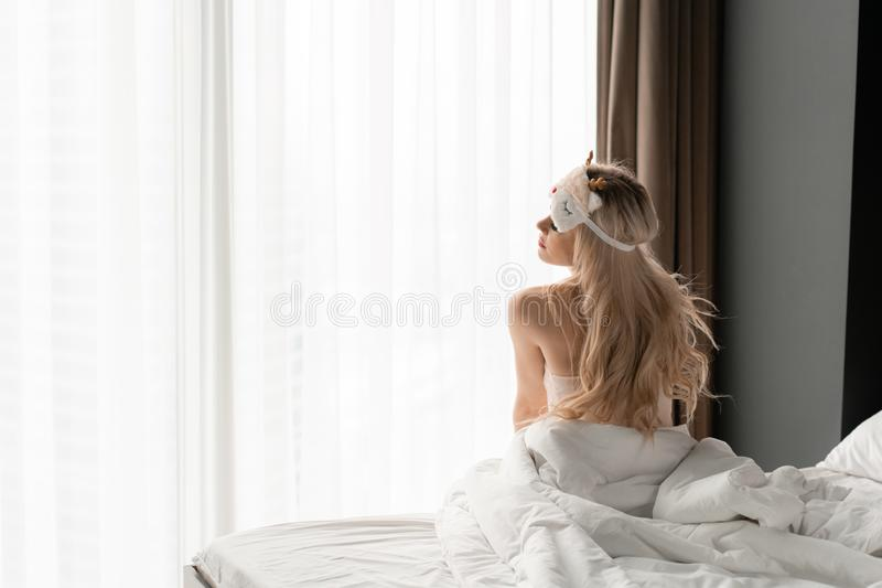 Ochtend in hotelruimte De jonge vrouw zit op comfortabel bed in masker voor het slapen op hoofd Groot venster op achtergrond stock fotografie