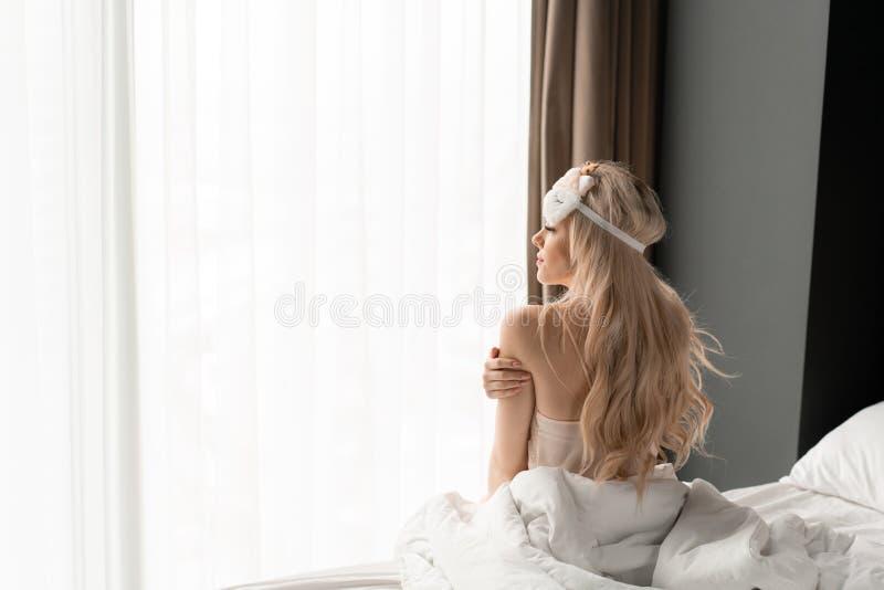 Ochtend in hotelruimte De jonge vrouw zit op comfortabel bed in masker voor het slapen op hoofd Groot venster op achtergrond royalty-vrije stock afbeelding