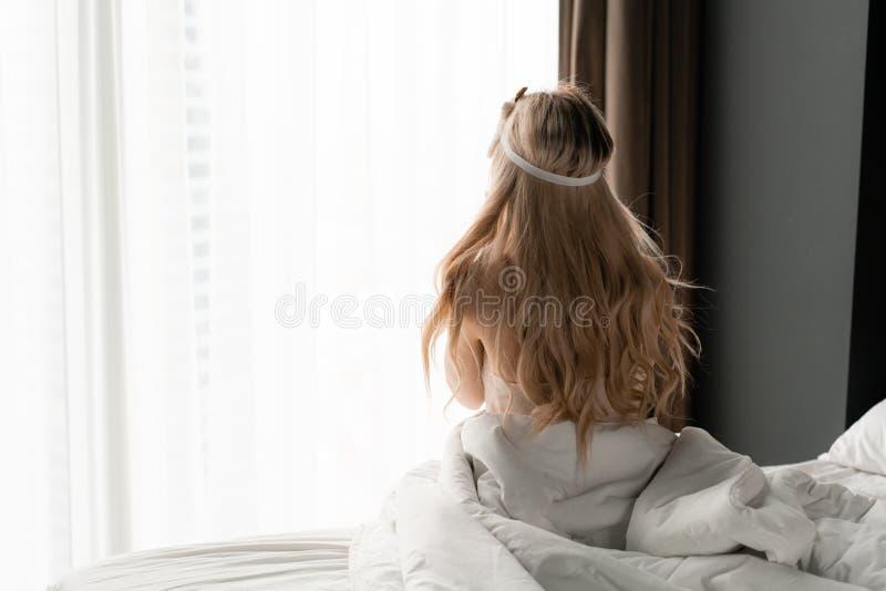 Ochtend in hotelruimte De jonge vrouw zit op comfortabel bed in masker voor het slapen op hoofd Groot venster op achtergrond royalty-vrije stock foto's