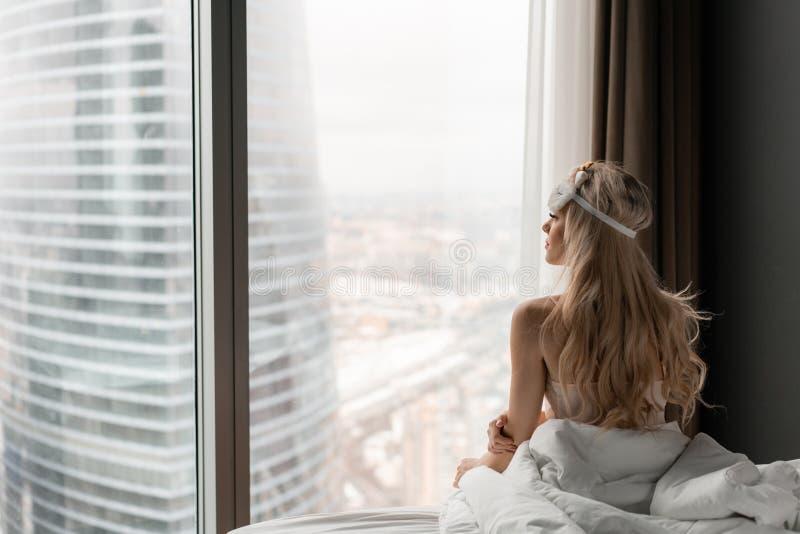 Ochtend in hotelruimte De jonge vrouw zit op comfortabel bed in masker voor het slapen op hoofd Venster van een wolkenkrabber  royalty-vrije stock foto