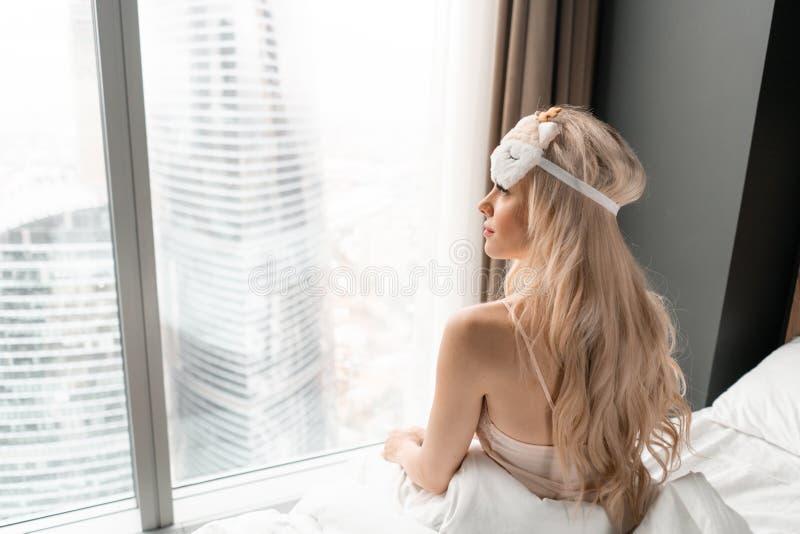 Ochtend in hotelruimte De jonge vrouw zit op comfortabel bed in masker voor het slapen op hoofd Venster van een wolkenkrabber  stock foto